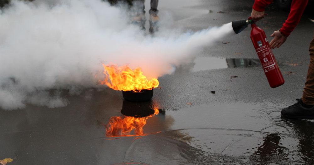 Homme éteignant un départ de feu avec un extincteur